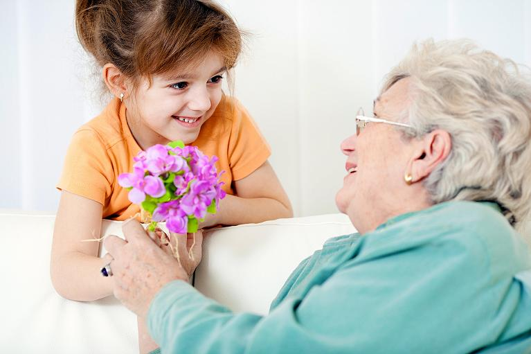 Granddaughter handing flowers to grandmother